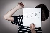 stock photo of scared  - Scared and abused young boy holding the paper with handwritten help sign - JPG