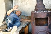 stock photo of homeless  - indignant Homeless Man  lies in a dilapidated structure with oven - JPG
