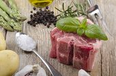 stock photo of lamb chops  - raw lamb chop with basil pepper garlic coarse salt potato and green asparagus on rustic wooden table - JPG