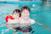 picture of floaties  - Young father and his little son having fun in an indoor swimming pool - JPG