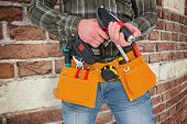 image of hammer drill  - Manual worker holding gloves and hammer power drill against red brick wall - JPG
