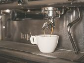 picture of dispenser  - Professional coffee machine with a small white cup ready for coffee being dispensed - JPG