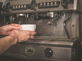 stock photo of dispenser  - The hands of a young woman is placing a cup under the dispenser of a professional coffee machine - JPG