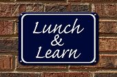 pic of lunch  - Lunch and Learn Sign A blue sign with the word Lunch and Learn on a brick wall - JPG