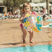 image of pool ball  - little cute girl playing near the pool with a ball - JPG