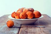 picture of sprinkling  - Sweet fried round doughnuts sprinkled with sugar powder on a plate - JPG
