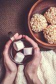 picture of crispy rice  - Woman holding cup of cocoa with marshmallows on woollens and rice crispy balls in wooden bowl - JPG