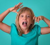 pic of growl  - Angry little girl growls isolated on turquoise background - JPG