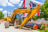 image of backhoe  - Excavator loader with backhoe is standing over blue sky in city street - JPG