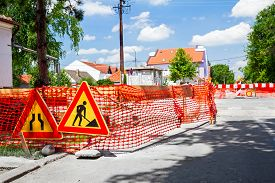 picture of safety barrier  - Construction site is protected by several signs and orange fence for safety - JPG