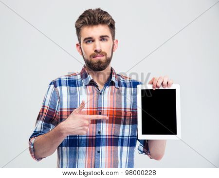 Portrait of a handsome man pointing finger on blank tablet computer screen isolated on a white background. Looking at camera
