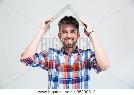 Happy man holding laptop on his head like roof of house isolated on a white background. Looking at camera