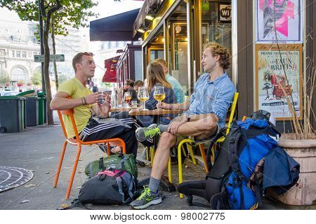 Two young men enjoying glass of beer in cafe in Paris