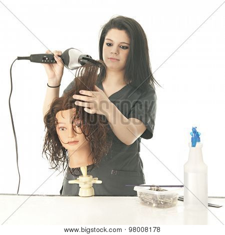 A pretty young cosmetology student drying and combing her practice mannequin's hair with her dryer.  On a white background.