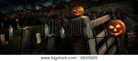 Duas abóboras de Halloween, sentando-se em cerca de