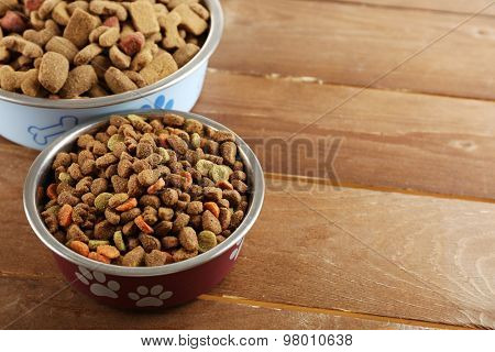 Dog food in bowls on wooden table