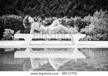 Black And White Bikini Asia Woman On Sunbath Longue By The Pool