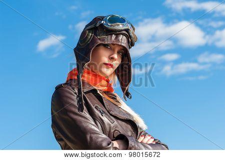 beautiful woman in aviator helmet on the sky background