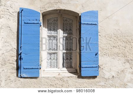 Old Window With Blue Shutters And Lace Curtain In A Rough-plastered Wall, Copy Space