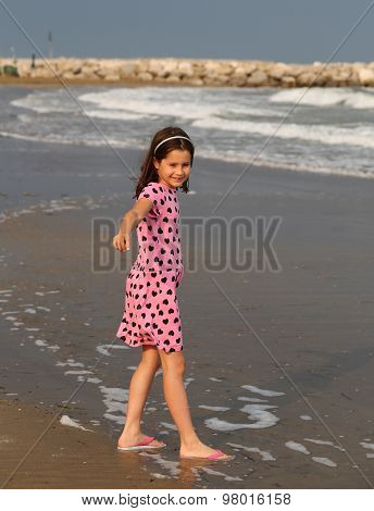 Beautiful Little Girl With Pink Dress With Small Black Hearts Of The Beach In Summer