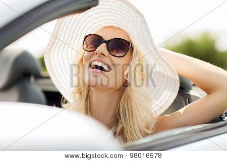 transport, leisure and people concept - face of happy woman in summer hat and sunglasses driving cabriolet car outdoors