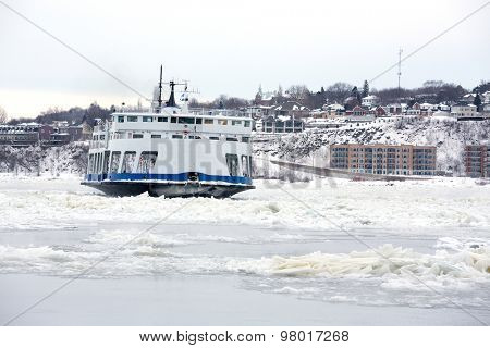 Passenger Ferry crosses the frozen St Lawrence river from Levis to Quebec City, Canada. Identifying marks removed.