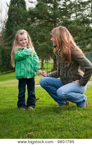 Niña sonriente mano de la madre en el Parque