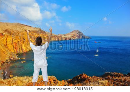 Quiet ocean cove on the island of Madeira. White sailing yachts lit sunset. The woman in the white practices yoga on an ocean coast