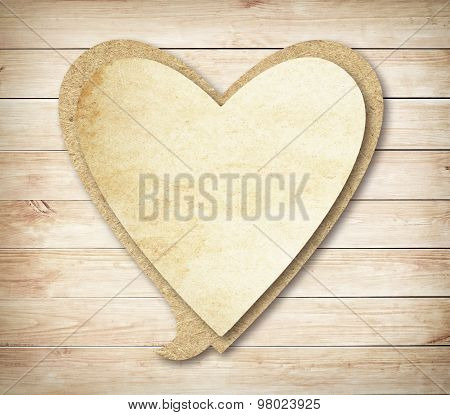 Heart paper speech bubble with shadow on brown wooden wall