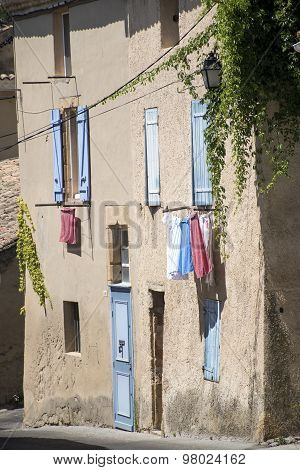 Typical House In South France With Blue Shutters And Drying Laundry Outside The Windows