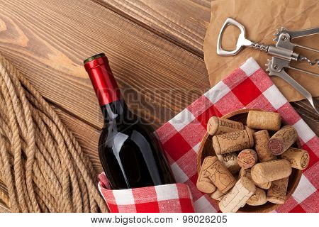 Red wine bottle, corks and corkscrew over wooden table background. Top view