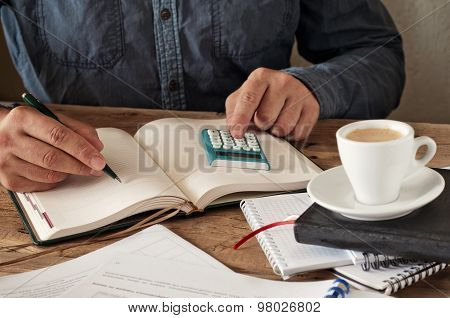 Hand Of Man Writing Something In Blank Notebook On Wooden Office Table