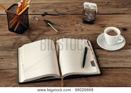 Open Blank Notebook On A Wooden Desk With A Cup Of Black Coffee, Pencils, Pens, Paper Clips, Ruler A