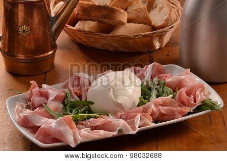 Sliced prosciutto ham and mozzarella cheese dish.