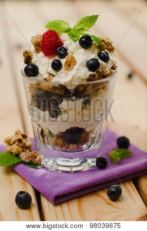 Sweet Fresh Cottage-cheese And Granola Dessert Topped With Blueberries, Raspberry And A Mint Leaf