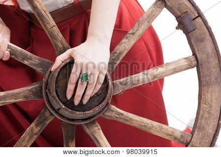 Vintage wooden wheel an woman's hand with a ring