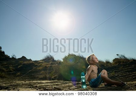 Boy sitting in the desert holding a blue bottle of water
