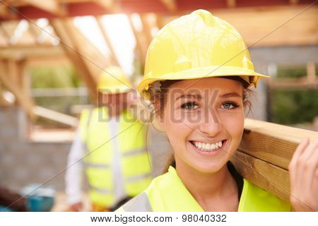 Builder And Female Apprentice Carrying Wood On Site