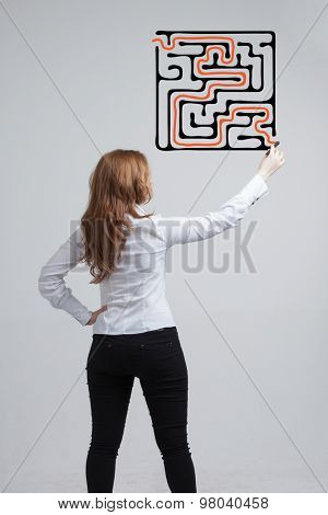 Young businesswoman finding the maze solution writing on the whiteboard.