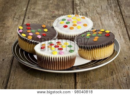 four cupcakes with dark and white chocolate icing and smarties on a plate