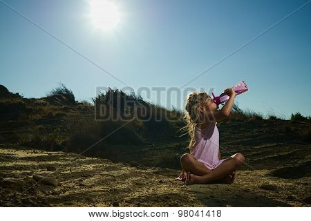 Girl Sitting In The Sand Under Hot Desert Sun Drinking Water