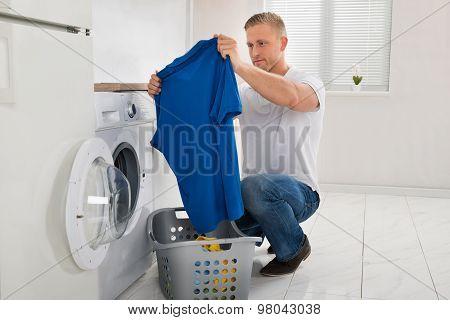 Man With T-shirt While Using Washing Machine