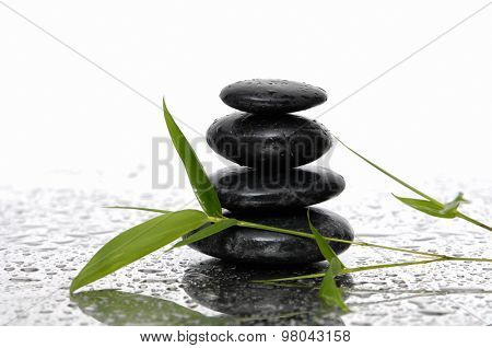 Still life with wet stacked stones with bamboo