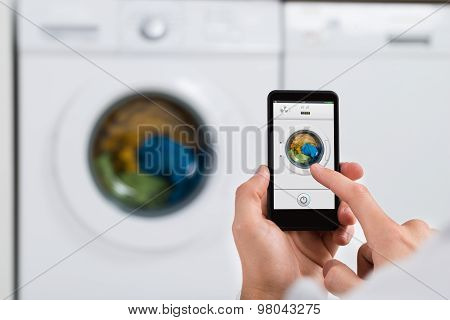 Person Hands With Mobile Phone Operating Washing Machine