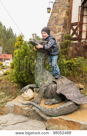 Boy playing near the statue of a dragon.