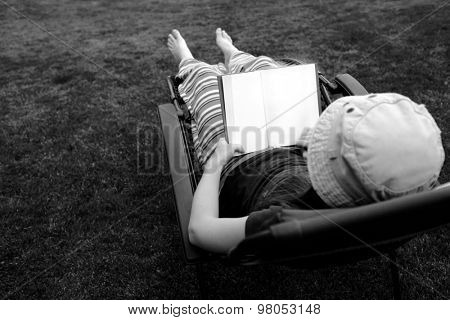 Photo of Person Lounging in Lawn Chair Relaxing and Reading Book