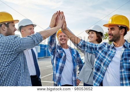 business, building, partnership, gesture and people concept - close up of smiling builders and architects in hardhats making high five outdoors