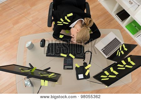 Businesswoman With Reminder Notes Sleeping In Office