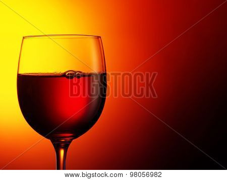 glass of red wine on dark red background. Filtered image: warm cross processed vintage effect.