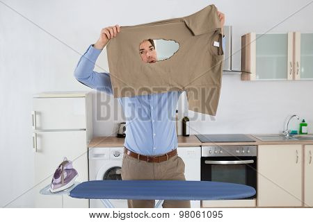 Man Looking At Burned Cloth With Electric Iron